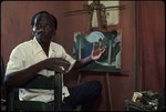 A Haitian painter in front of a painting on an easel
